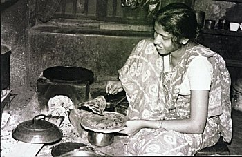A Konkani Woman Making Pan Cakes on Wooden Stove