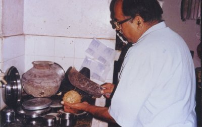 Kamat Breaks Open a Coconut for Cooking