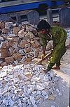 Girl breaking heavy stone with a hammer