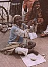 A blind street beggar plays flute through his nose, Bangalore