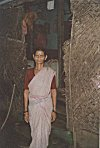 Rural woman in cotton sari in front of her thatched hut