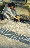 a girl drawing rangoli