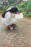 a girl looking in to a book and  drawing rangoli