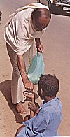 A barefooted Brahmin offers alms to a beggar