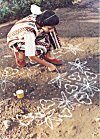 This school girl wears colorful dresses to draw her rangoli.