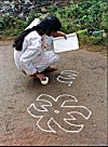 A Girl Learning Rangoli by Looking at a Book