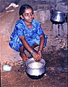 A Young Girl Washing Dishes by the Roadside