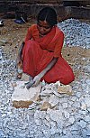Woman handbreaking granite stone