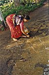 Woman Laying Rice Powder to form Kolam