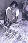 Smiling Woman Weaving a Mat